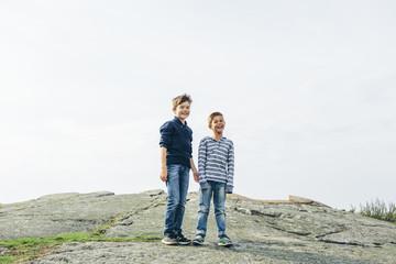 Sweden, Blekinge, Karlskrona, Boys (8-9) standing on asphalt mound and laughing