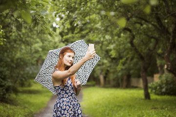 Finland, Pirkanmaa, Tampere, Woman wearing floral dress standing with umbrella in park and taking selfie