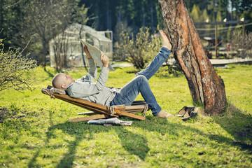 Finland, Paijat-Hame, Heinola, Mid adult man reading newspaper on sunlounger