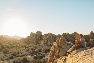 USA, California, Joshua Tree National Park, Man sitting on rock and looking at rocks