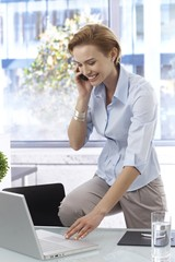Happy businesswoman talking on mobilephone