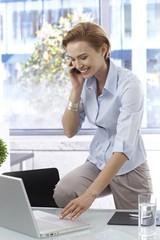Happy businesswoman talking on mobilephone