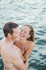 Sweden, Vastmanland, Mid adult couple embracing in sea