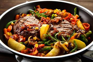 Roast steak with vegetables served on frying pan