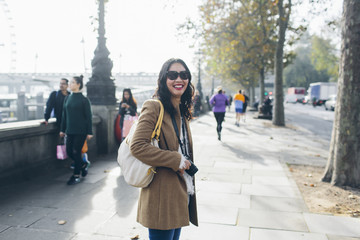 UK, England, London, Smiling woman standing on pavement at Victoria Embankment