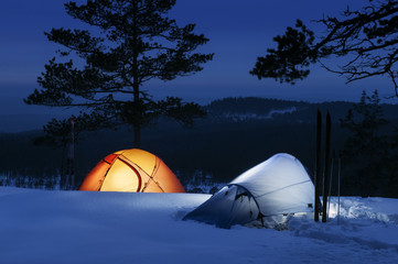 Sweden, Vastmanland, Bergslagen, Kindla Naturreservat, Illuminated tents on snow with forest covered mountain in background