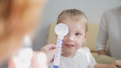Check up of eyesight in child's ophthalmology - optometrist diagnosis little girl