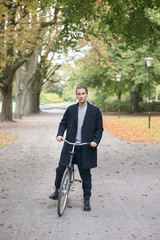 Sweden, Skane, Malmo, Man standing with bicycle in park