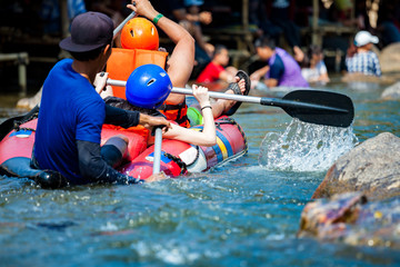 Young men and women are rafting on the river, extreme and fun sport at tourist attraction