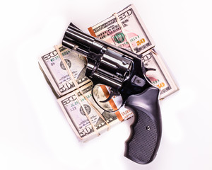 hand gun and stacks of $50s