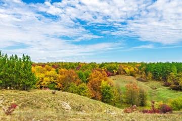 Bright blue sky and clouds in the autumn day over the hills. Nature landscape.