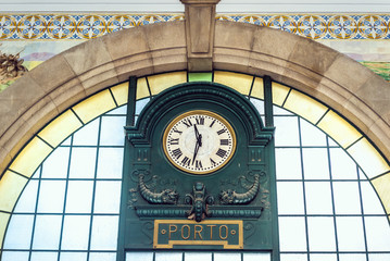 Old clock in Sao Bento railway station in Porto city in Portugal
