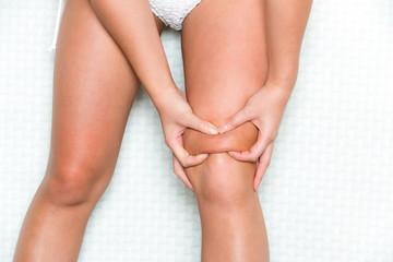 膝の上の脂肪をつまむ女性