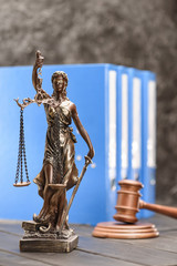 Close-up view of antique statue of lady justice on wooden table, Law concept
