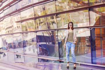 Young woman with bob hair cut, eyeglasses, in beige jacket and boyfriend jeans standing near glass building. Street fashion. Smart casual