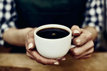 Female waitress in apron holding hot coffee mug indoors.