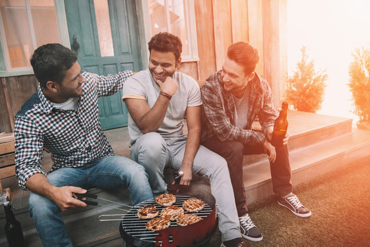 Three young men drinking beer and smiling while sitting on porch and making barbecue