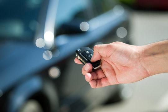 Man hand press the remote control car alarm systems