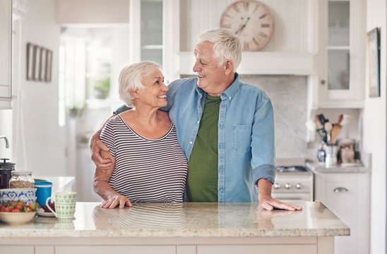 Content seniors standing in each other's arms together at home
