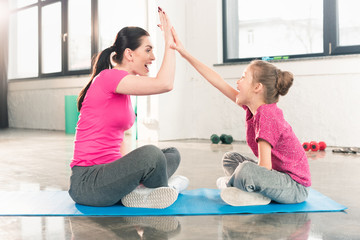 Side view of happy mother and daughter sitting on yoga mat and giving high five in gym