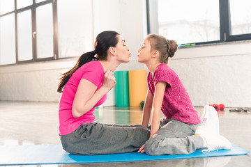Side view of happy mother and daughter sitting on yoga mat and kissing