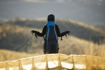 Paraglider is preparing for the flight on mountain. Extreme sports activity.
