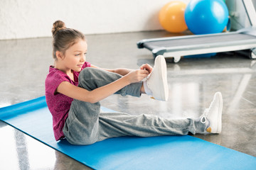 Adorable little girl in sportswear sitting on yoga mat and tying shoelace