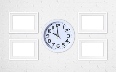 Alarm clock and four blank photo frames on white bricks wall, office style interiors mock up
