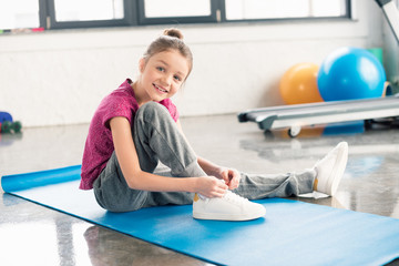 Adorable little girl in sportswear tying shoelace and smiling at camera