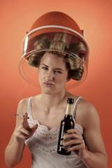 Frau trinkt und raucht schlecht gelaunt unter Trockenhaube