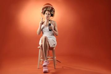 Frau mit Lockenwickler unter Trockenhaube mit Bier und Zigarette