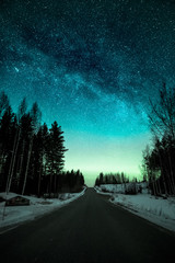 Night sky with weak aurora borealis by a road