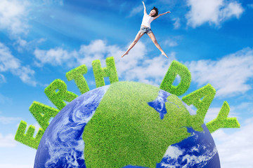 Woman jumps above green globe