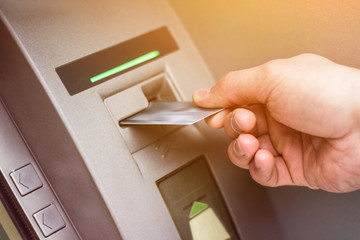 Hand of a man with a credit card, using an ATM. Man using an atm machine with his credit card.