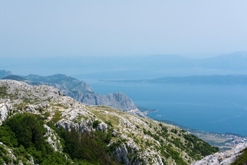 Top view on blue fogged sea bay from the mountain cliffs of Biokovo highland area in croatian national park near Makarska resort.