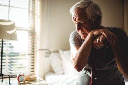 Thoughtful senior man with his walking stick in the bedroom