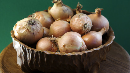 wooden bowl with onions and green background