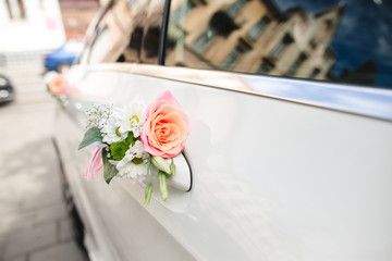 Pink rose and daisy put on handle of car door