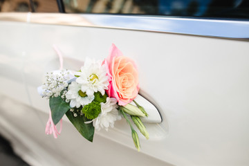 Daisies and rose put on handle of car door
