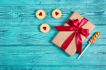 Gift box with a satin bow on a blue wooden background. A present, a cookie with marmalade and a lollipop. Holiday romantic concept. Copy space. Flat lay