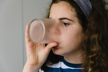 young girl drinking water and eating  at home with smartphone on the table