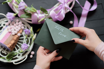 Green envelope with love on black wooden background with flowers and white wreath and blueberry cake