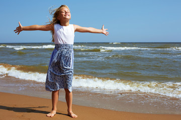 Happy child stands on the shore of the ocean with arms outstretched