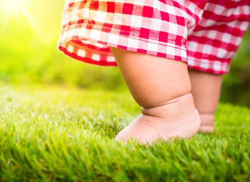 Baby standing on green grass with sunlight
