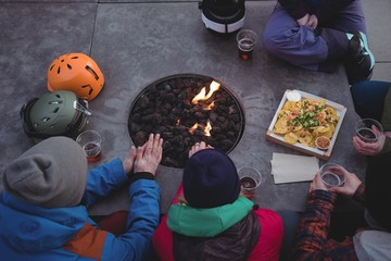 Group of skiers rubbing their hands near fireplace