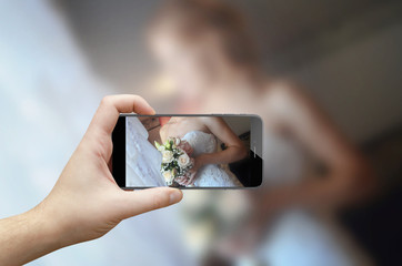 Taking picture of bouquet in bride hands with focus on flowers