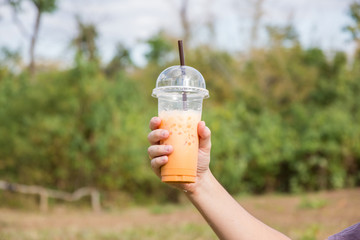 hand holding ice milk tea