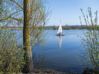 Deurstickers Zeilen A sailing dinghy and its reflection on a peaceful blue lake, conningbrook lakes country park, with trees in the foreground.
