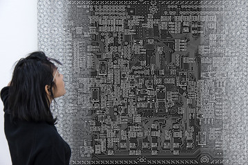 Woman is looking large plan motherboard. Visitors viewing the exhibition of modern art with electrical equipment of computer.