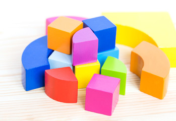 Colored wooden blocks, cubes, build on a light wooden background.